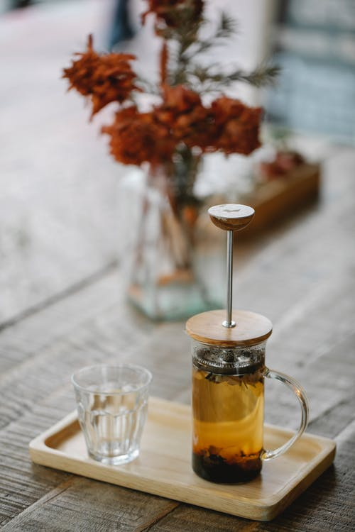 Teapot and glass on tray in cafe