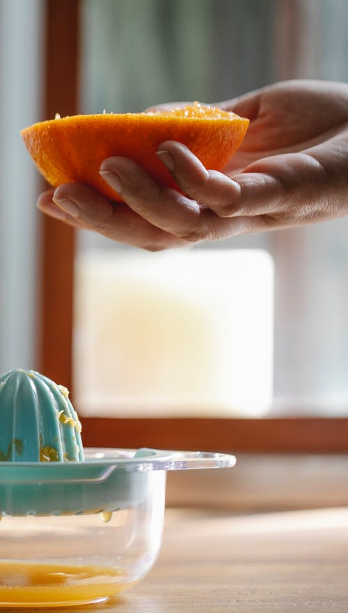 Crop anonymous person holding orange half above table with plastic orange juicer in light kitchen