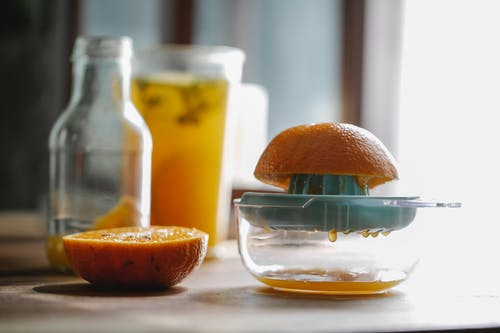 Half of delicious sweet orange placed on plastic orange juicer placed on kitchen table