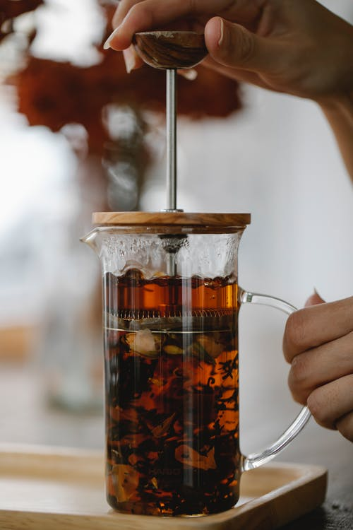 Crop anonymous female touching glass French press teapot with brewing aromatic black tea placed on tray