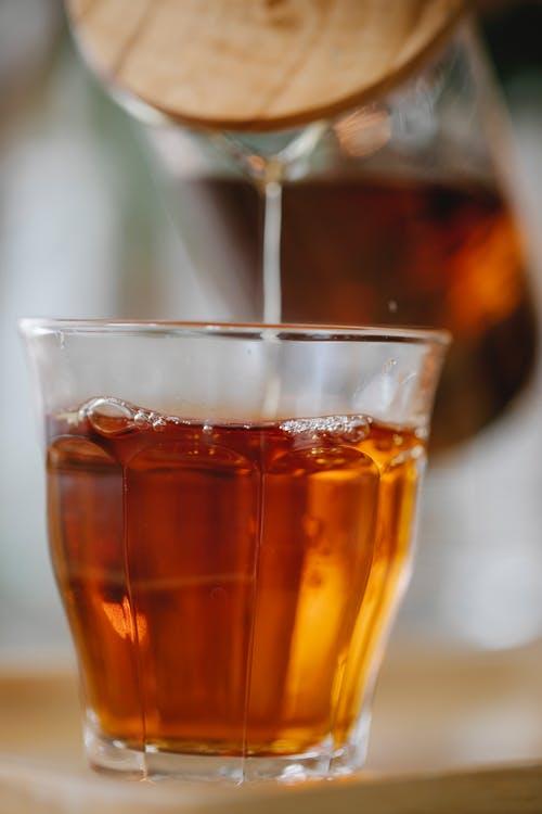 Herbal black tea pouring into glass