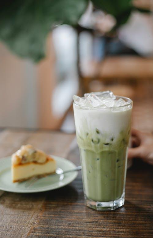 Glass of tasty refreshing matcha latte served on table with yummy pie slice in cafe