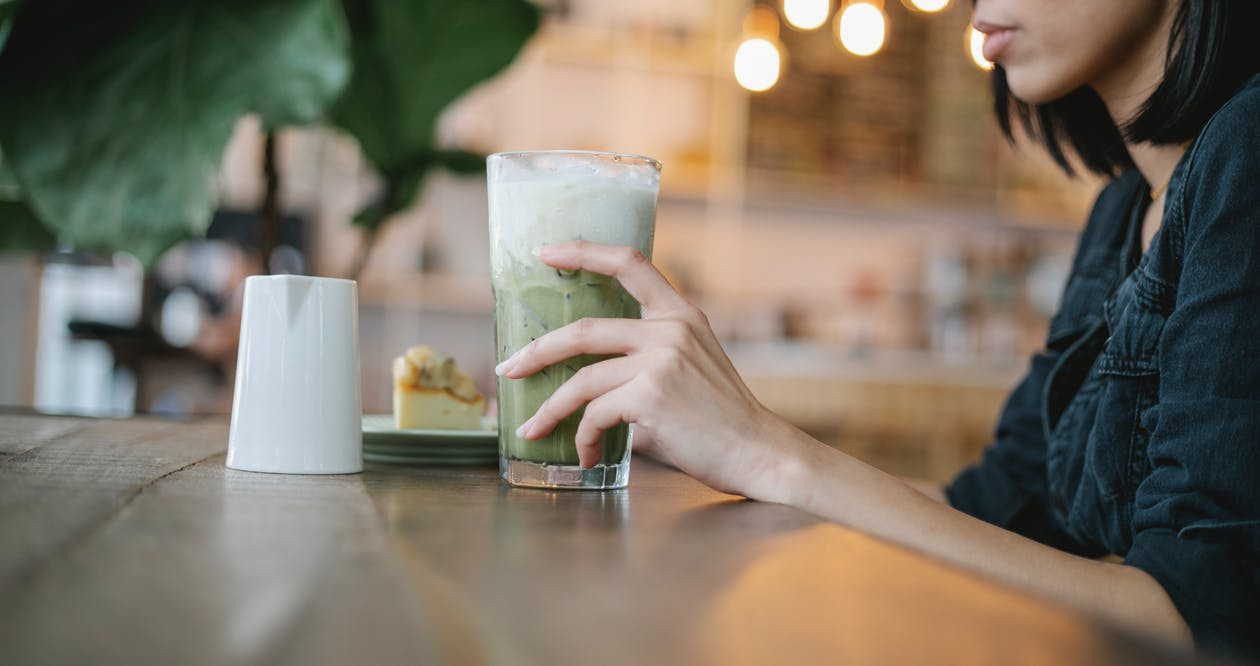 Crop woman drinking iced matcha latte in modern cafe