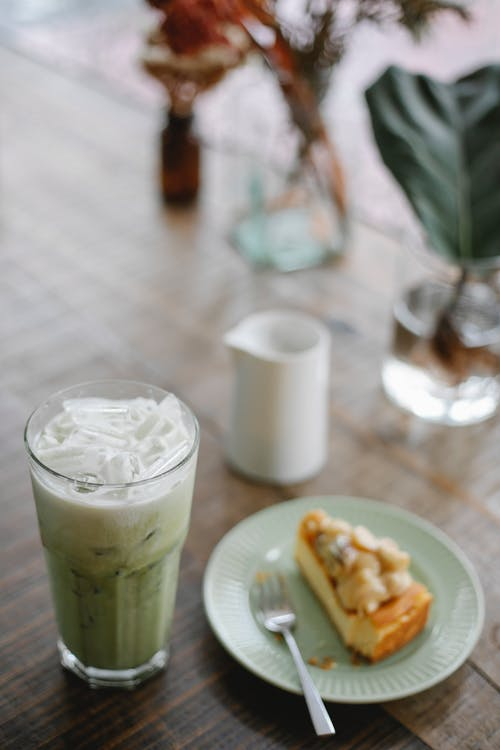 High angle refreshing iced matcha latte served on table with sweet cake slice in light room