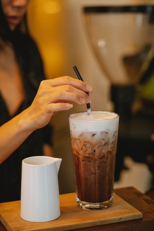 Crop woman putting straw into glass of iced coffee latte