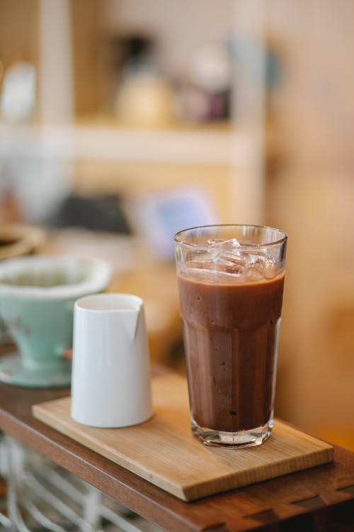 Delicious iced coffee on wooden board with milk jigger