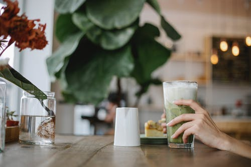Crop unrecognizable woman drinking refreshing matcha latte in cafe