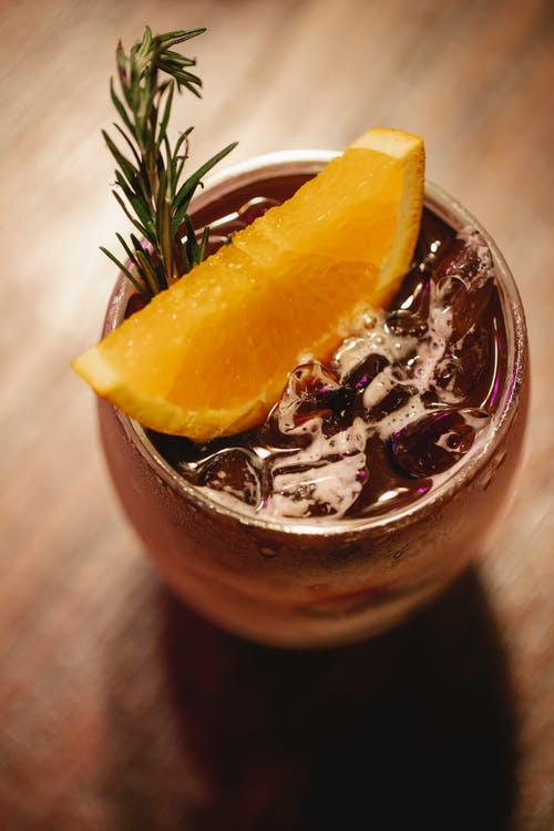 From above glass of tasty fruit iced mocktail garnished with orange slice and fragrant rosemary twig