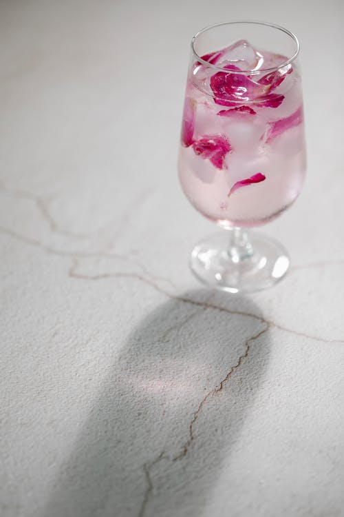 Glass of cold refreshing iced water with pink rose petals served on white table