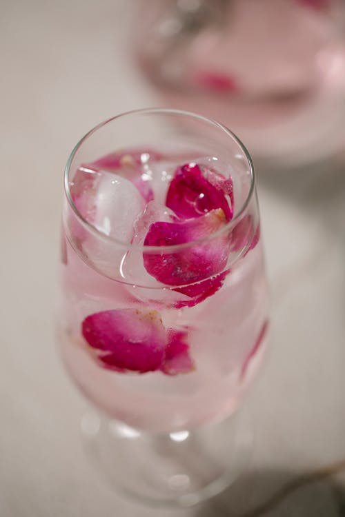 From above glass of refreshing iced water with tender pink rose petals placed on white table