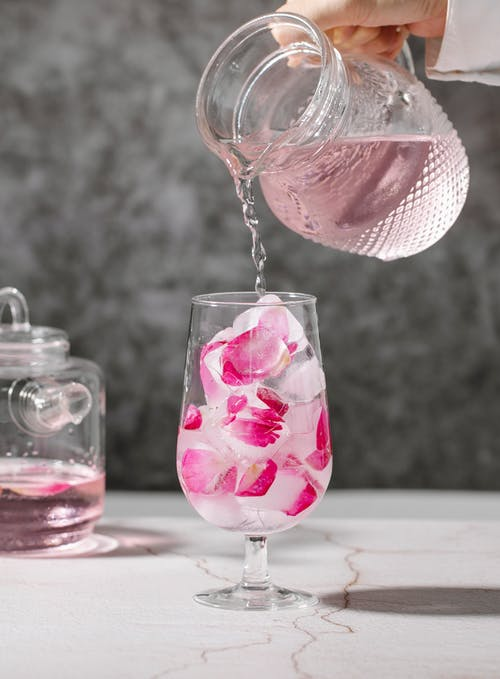 Crop faceless bartender pouring drink from crystal jar into transparent glass full of ice cubes with pink rose petals