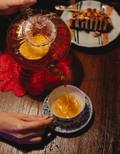 Crop person pouring tea with lemon