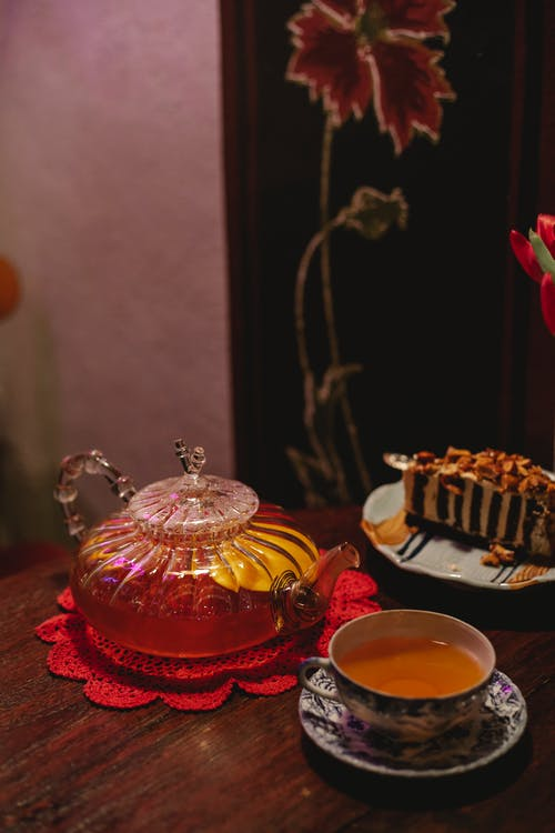 High angle of cup full of hot aromatic tea placed on table near crystal teapot and plate with dessert in cafe