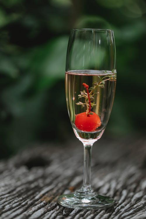 Crystal glass of alcoholic cocktail with cherry and mint on wooden table against blurred background