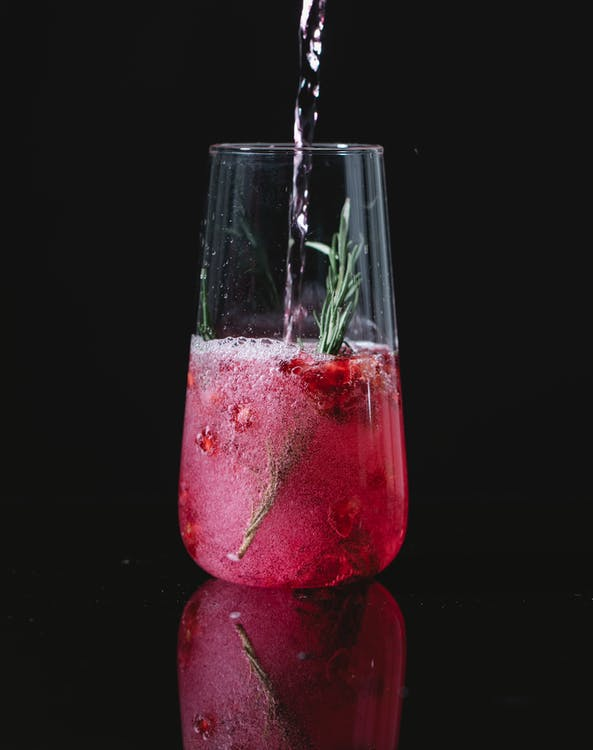 Crystal clean glass of red cocktail with berries and rosemary on black background