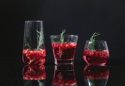 Transparent clean glasses filled with similar red cocktail with rosemary and berries on black background