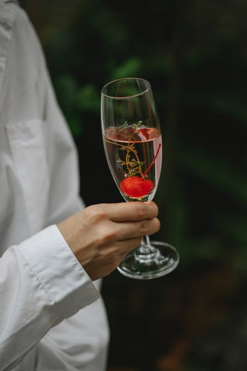 Crop unrecognizable female in white shirt with crystal clean glass filled with alcoholic cocktail with cherry