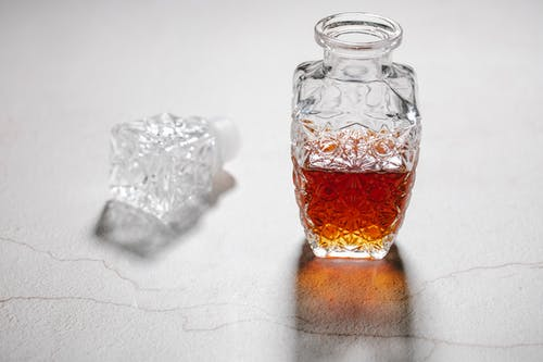 From above of open crystal glass jug with alcoholic beverage placed on white table with cracks