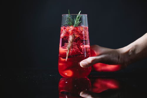 Crop woman with glass of red cocktail