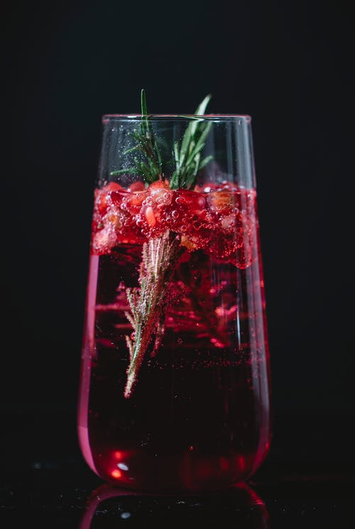 Crystal glass of alcohol cocktail with pomegranate berries and rosemary twig against black background