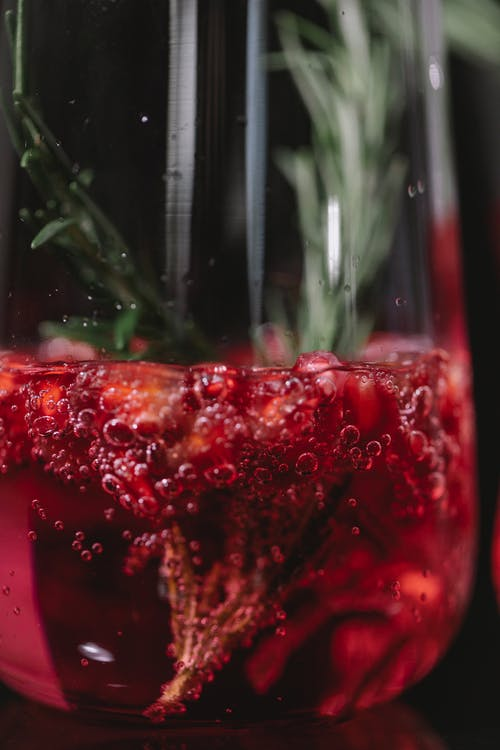 Fizzy cocktail with red berries and rosemary