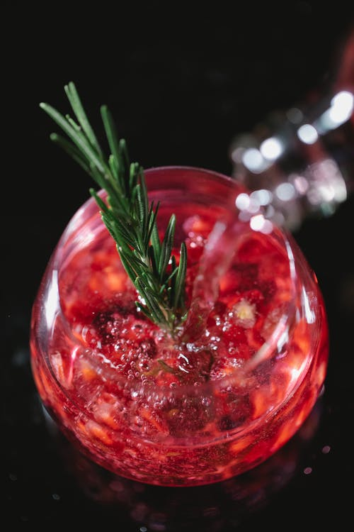 From above of crystal glass of pomegranate champagne cocktail served with rosemary sprig on black table