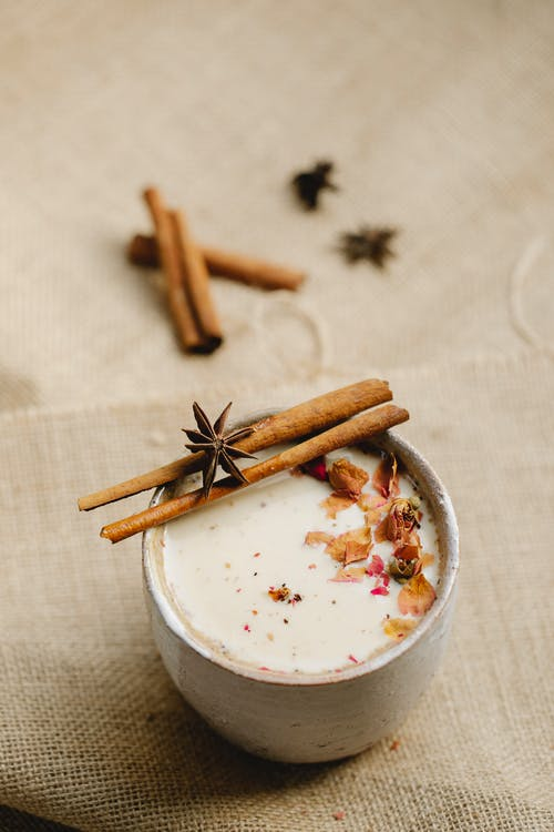 From above composition of tasty homemade chai tea served in ceramic mug with star anise on sticks of cinnamon and other spices placed on gray linen tablecloth