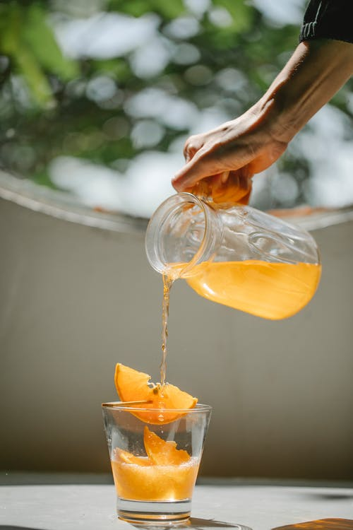 Crop woman pouring cold orange beverage into glass