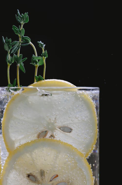Closeup of refreshing sparkling lemonade served in transparent glass with slices of lemon and stem of thyme