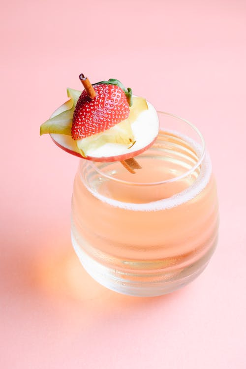 High angle of wide transparent glass with fruit cocktail decorated with slices of strawberry starfruit and apple on cinnamon stick placed on pink surface