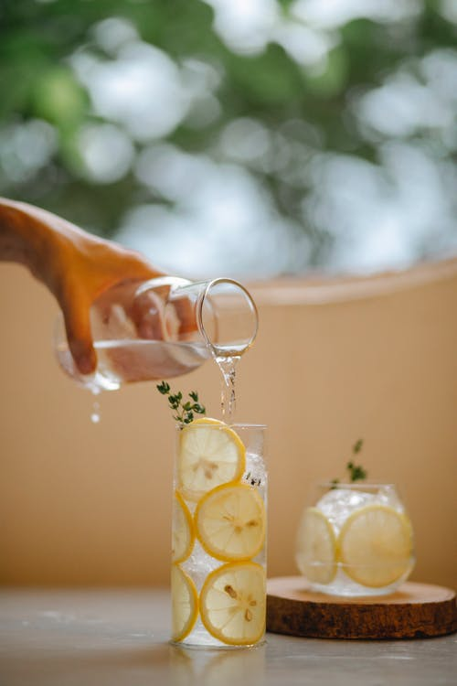 Crop person pouring water in lemonade