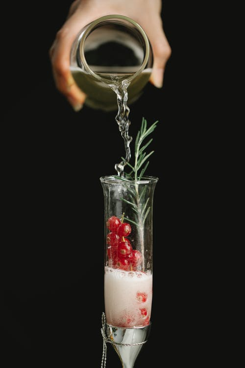 Crop woman pouring drink into glass
