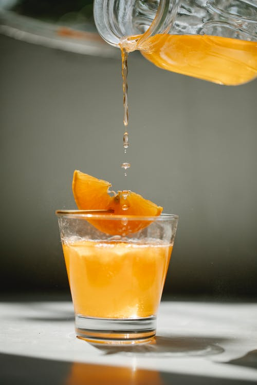 Nonalcoholic drink poured from crystal jar into transparent glass decorated with piece of orange on thin wooden stick