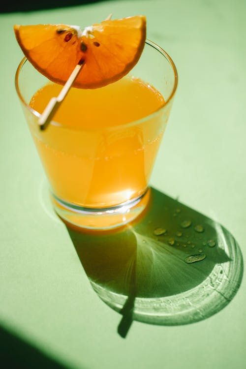 Glass of refreshing drink with orange