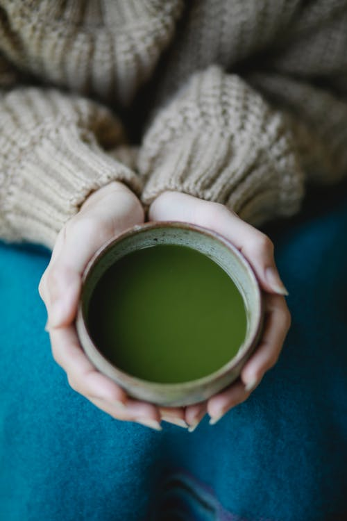 Crop woman with cup of matcha