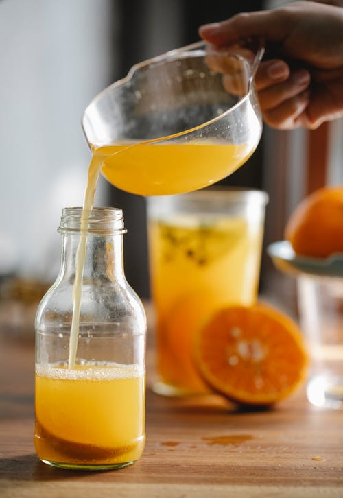 Crop anonymous person pouring fresh homemade orange juice from plastic bowl of squeezer into glass bottle