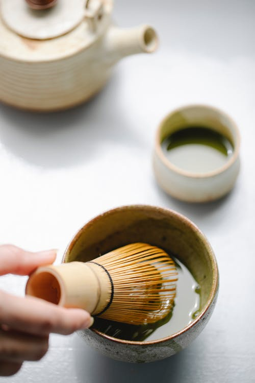 Crop woman whipping matcha tea