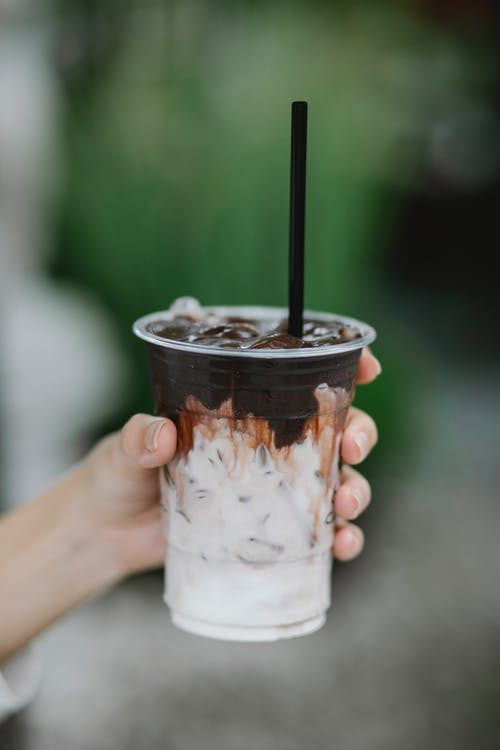 Crop anonymous person with disposable plastic cup of ice coffee with black straw on blurred background