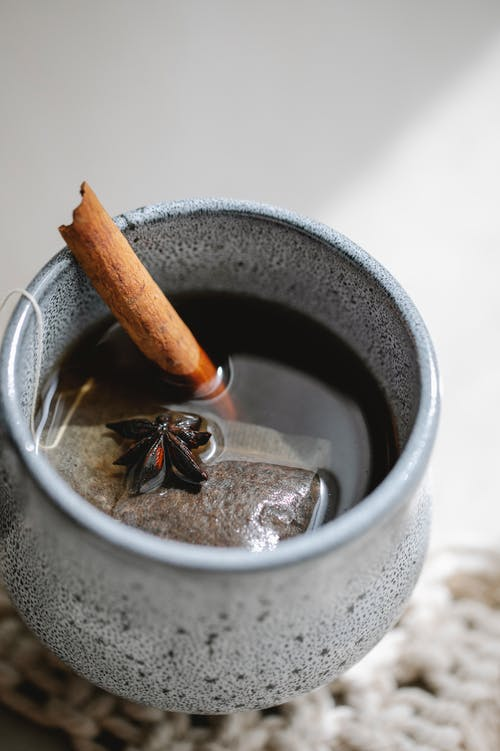 From above of hot aromatic tea with stick of cinnamon and star of anise brewed with teabag in cup