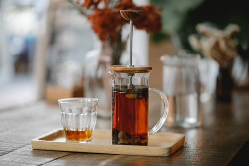 Transparent French press with hot aromatic herbal tea brewing on wooden tray near glass on table in cafe