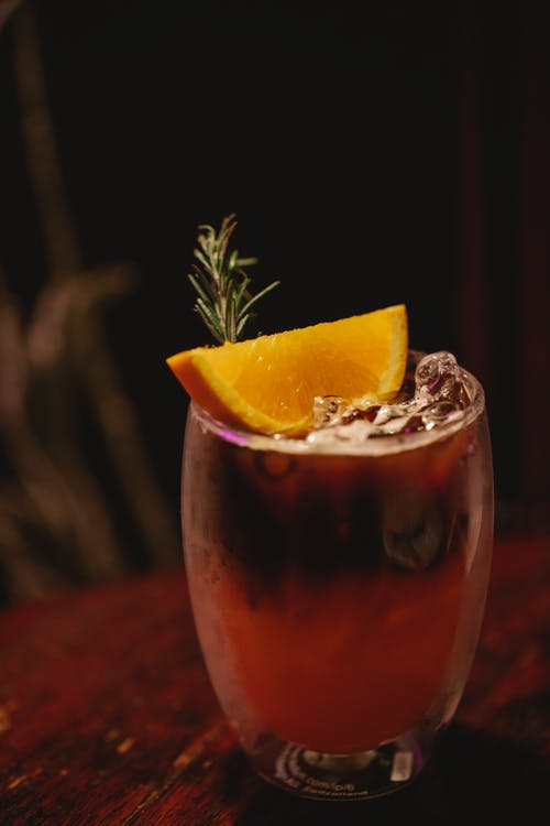 Crystal clean glass of alcoholic drink with ice cubes and decorated with slice of orange and rosemary on table in bar