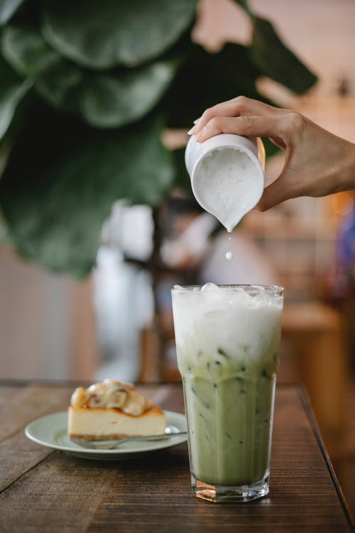 Crop anonymous female pouring whipped milk into glass with matcha frappe placed on table near plate with dessert in cafe