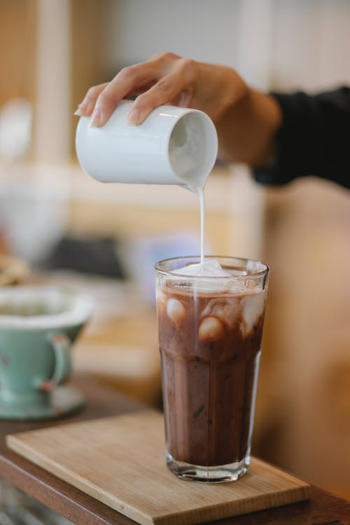 Crop anonymous female barista adding whipped milk in transparent glass with ice coffee placed on wooden board