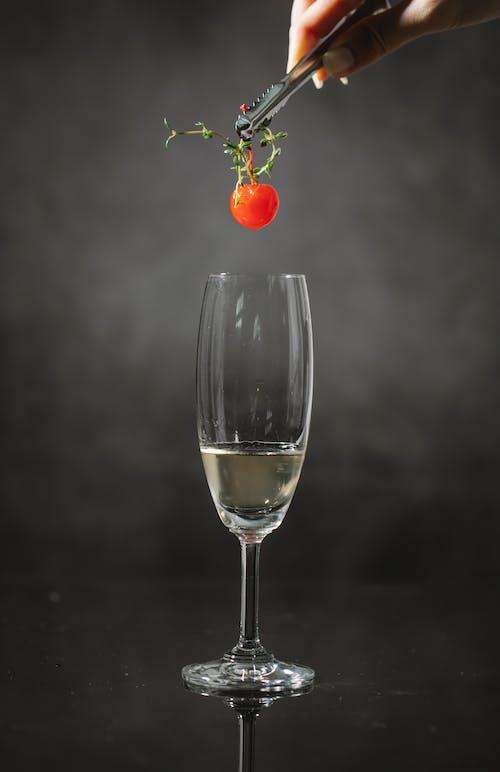 Crop woman adding cherry in drink