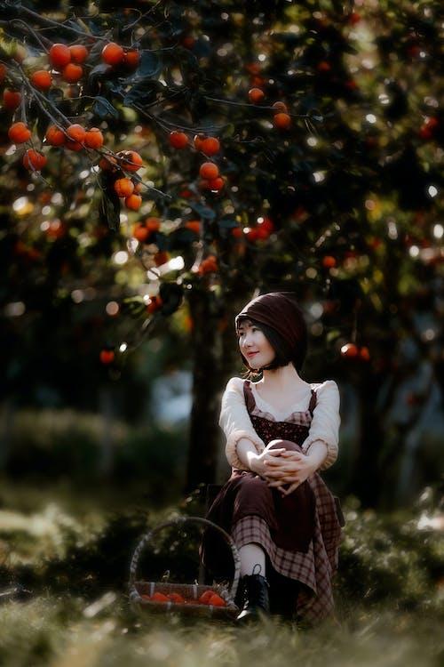 Peaceful Asian woman sitting under fruit tree