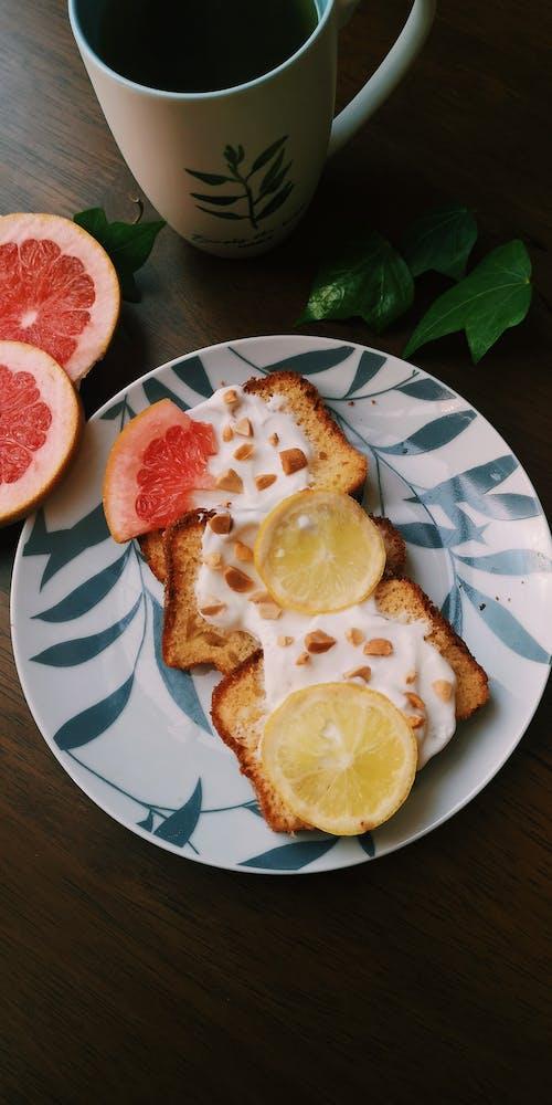 Sliced Lemon on Toasts with Yoghurt and White Mug on Wooden Table