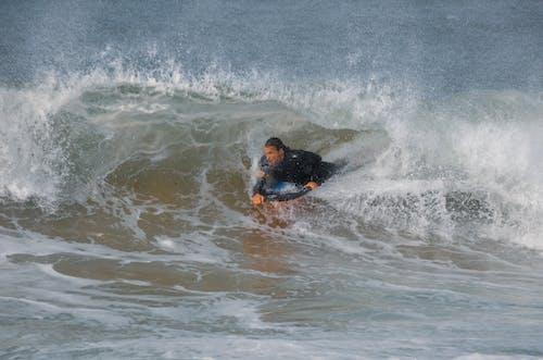 Man in Black Wetsuit Surfing
