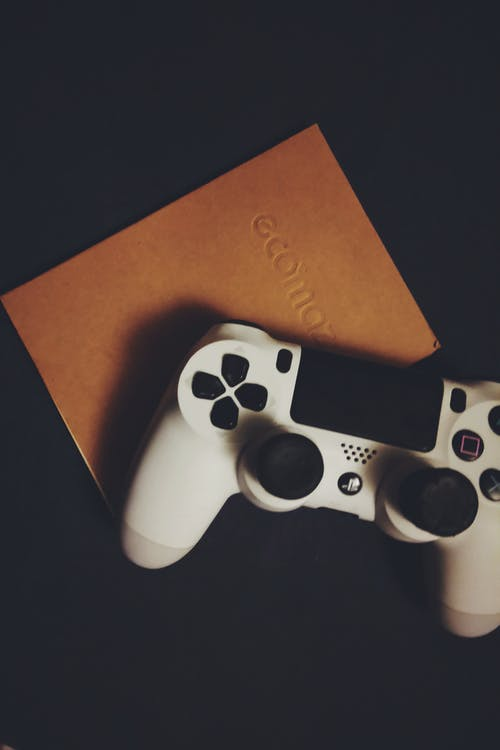 White Dualshock 4 on Brown Book