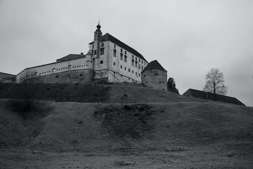 Ancient castle built on hill under cloudy sky