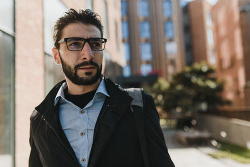 Selective Focus Photo of a Man with Eyeglasses Looking Away